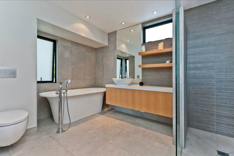Modern bathroom with a free-standing tub clad in stone tiles
