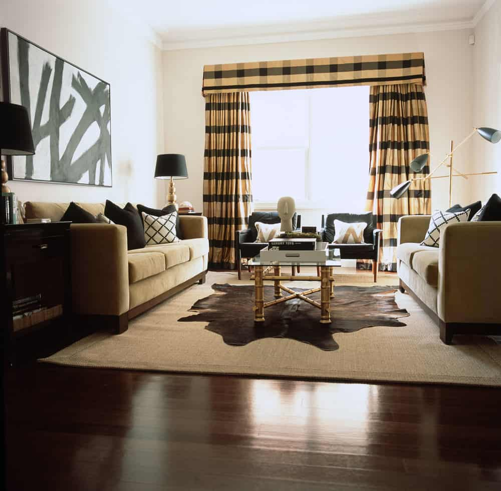 camel-black-living-room-plaid-window-dressing-sisal-rug-black-side-table-and-cushions-bamboo-glass-coffee-table-hide-rug-charcoal-lounge-chairs-vintage-lamps-floorboards-timber-diane-bergeron