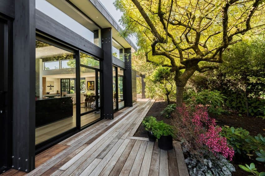 A wooden deck surrounds the house