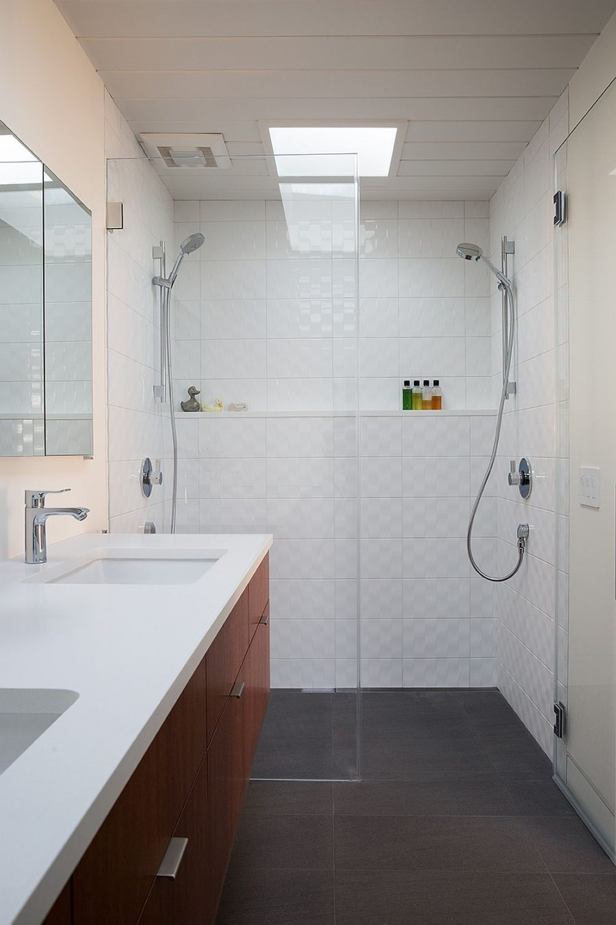 Bathroom is finished with textured white tiles while wooden vanity echoes the main theme