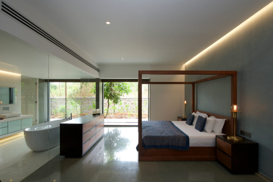Bedroom and bathroom are both connected and divided with a glass wall between them