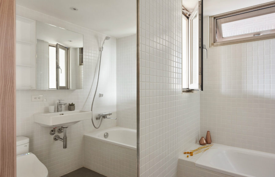 Entirely tiled bathroom features a big mirror to maximize space at least visually