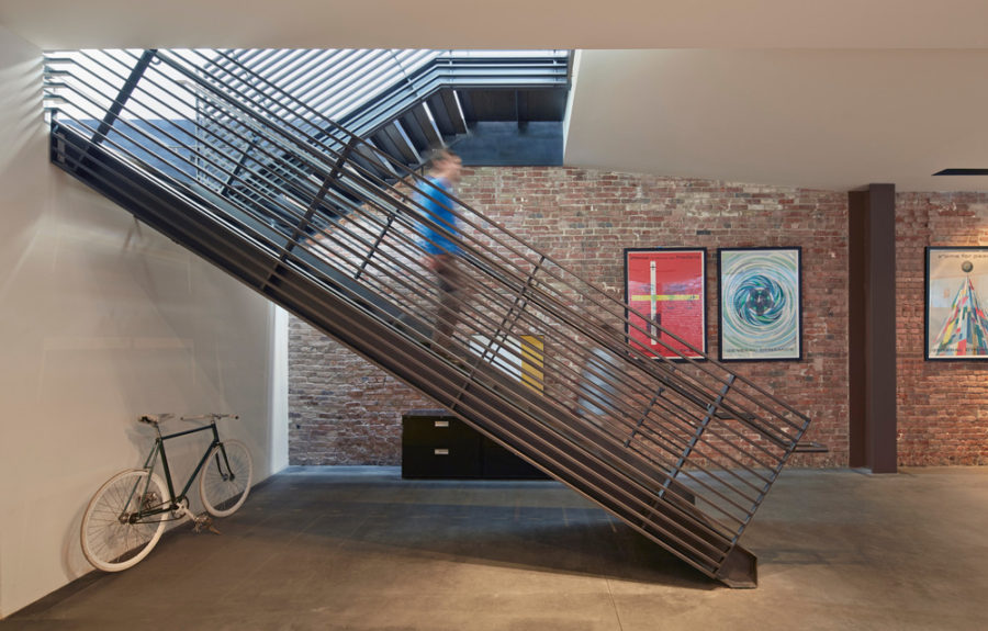 Exposed brick contrasts nicely with the metallic staircase and bright artworks