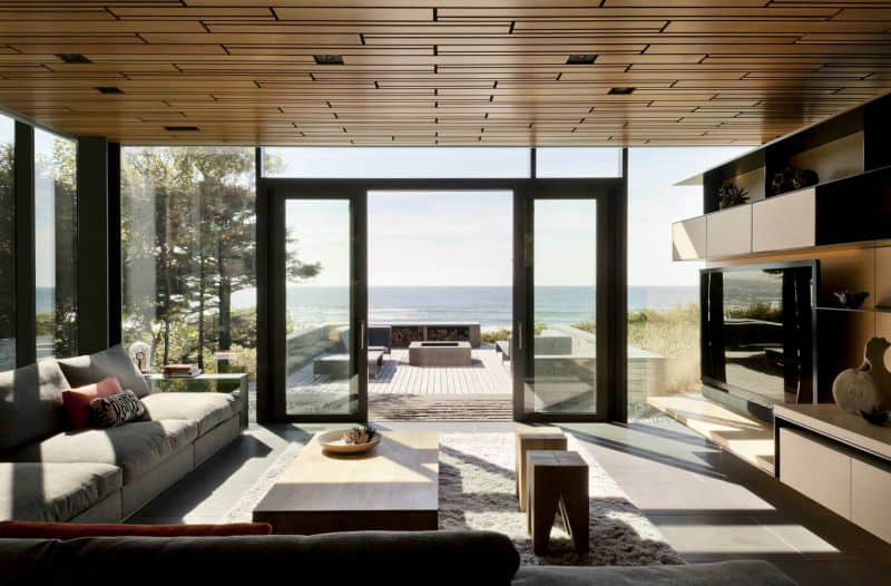 Indoor outdoor living area extends to the wooden terrace with a firepit
