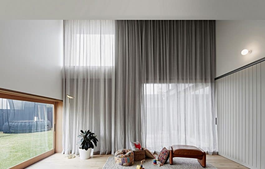 Living area features long curtains that shield it from both windows