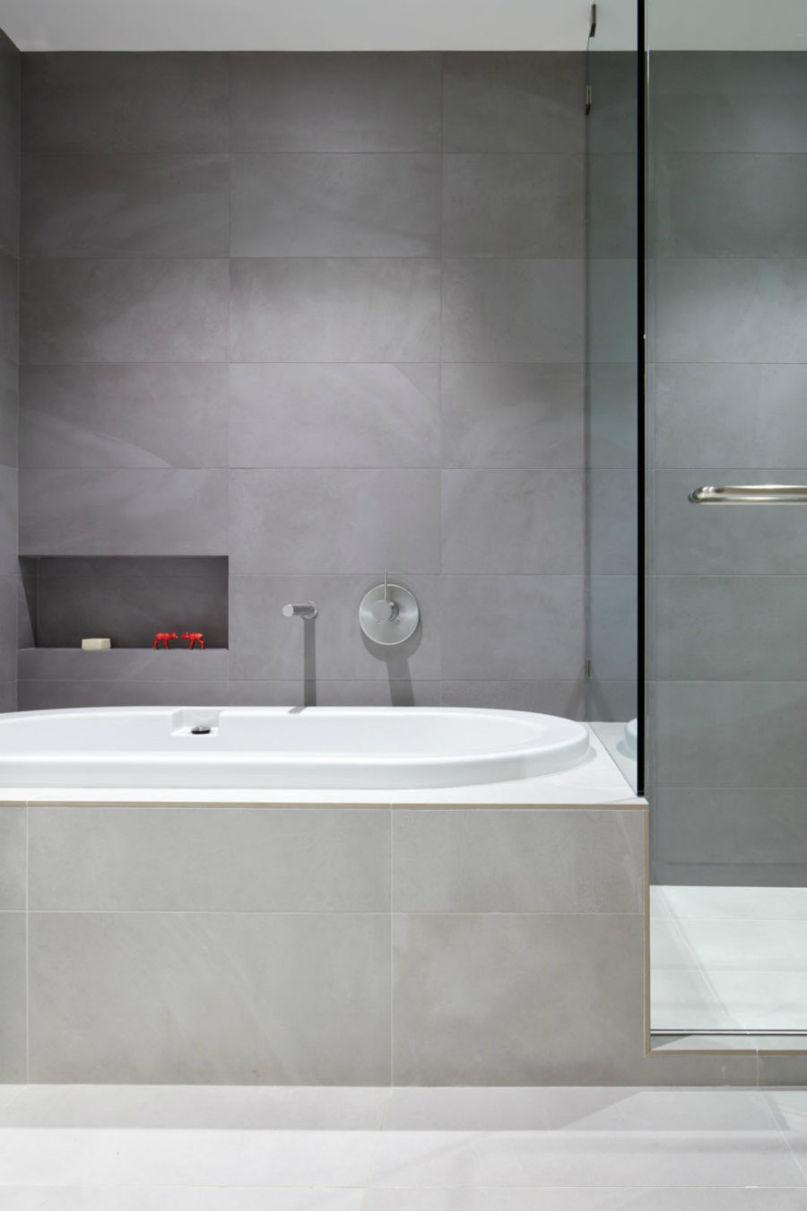 Modern minimalist bathroom features a bathtub and a glass shower stall