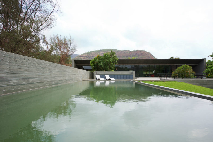 Natural swimming pool sits next to a green hill