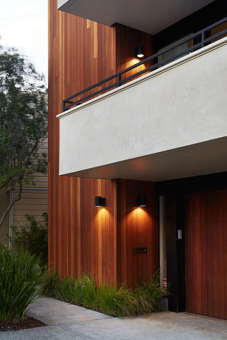 Plastered white balconies contrast with wood siding