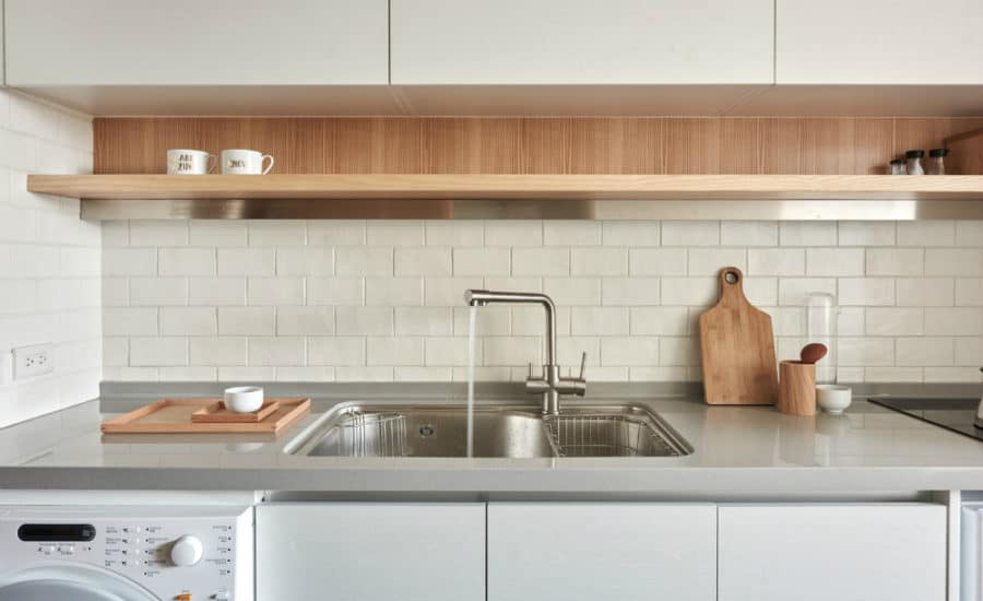 Simple tiles wrap around the kitchen walls to make cleaning easier