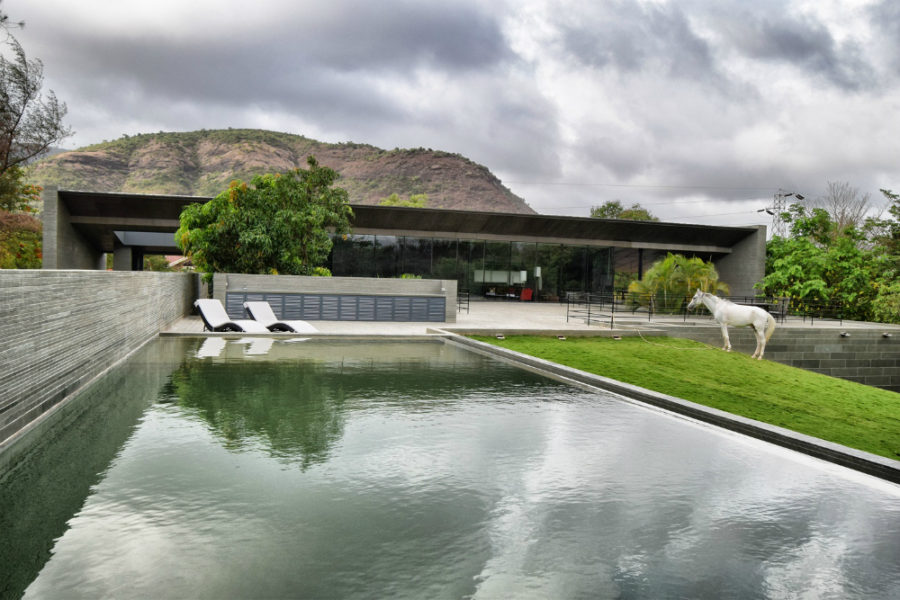 The mountainous hill makes a beautiful backdrop for the modern home 900x600 Incredible Malavli Residence Sits on a Man Made Mound