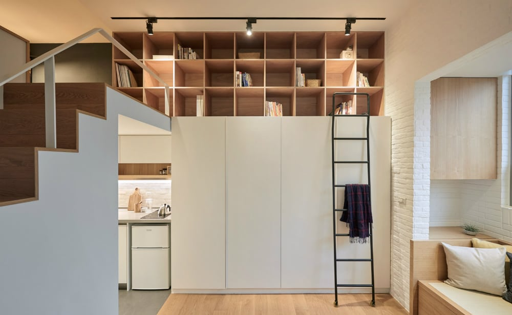 Wall storage includes a wardrobe and a built-in shelving for books and display objects