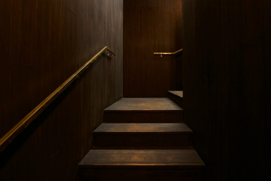 Wood-clad staircase with golden brass railing makes for luxurious feel