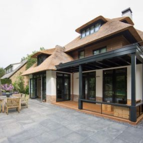 A stone paved patio stands right in front of a dining room inviting to continue dinner in refreshing outdoors 285x285 Striking Villa Naarden Is a Modernized Dutch Thatched House