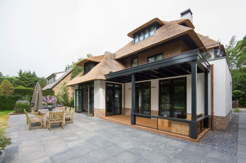 A stone-paved patio stands right in front of a dining room inviting to continue dinner in refreshing outdoors