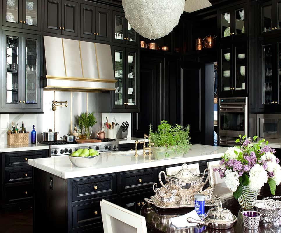 Black kitchen with a stainless steel backsplash by Kirsten Kelli