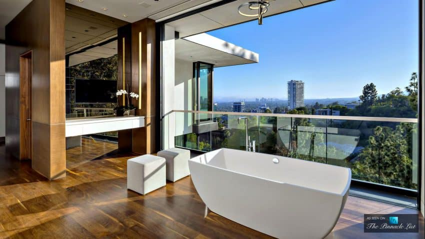 Luxury bath has an indoor outdoor feel thanks to glass balcony railings