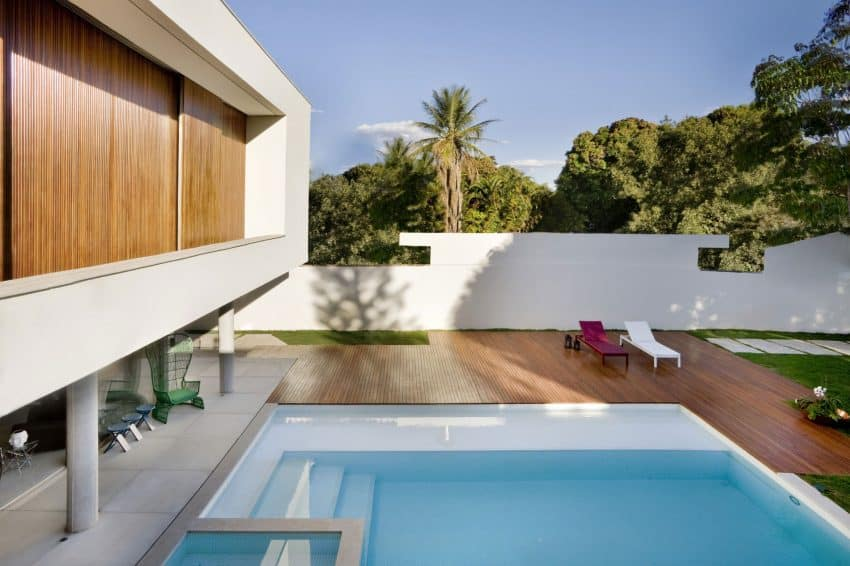Roomy swimming pool deck enjoys privacy from the fence and green landscapes