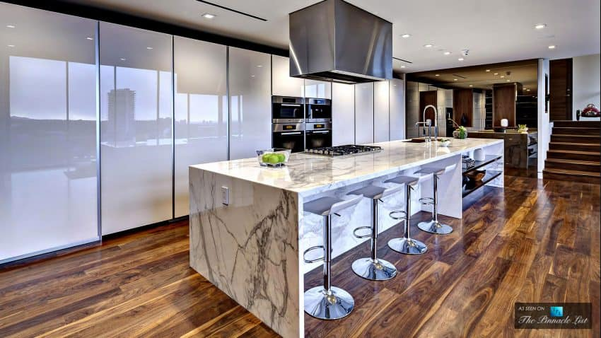 Spacious open kitchen features a luxurious marble kitchen island of unreal size
