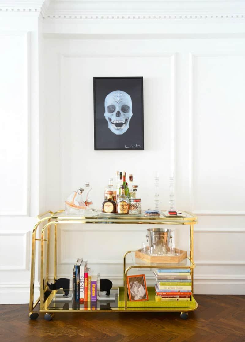 Golden bar cart with a glass shelf