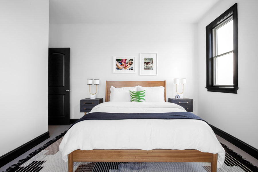 Monochromatic bedroom looks warmer thans to a natural wood bed frame