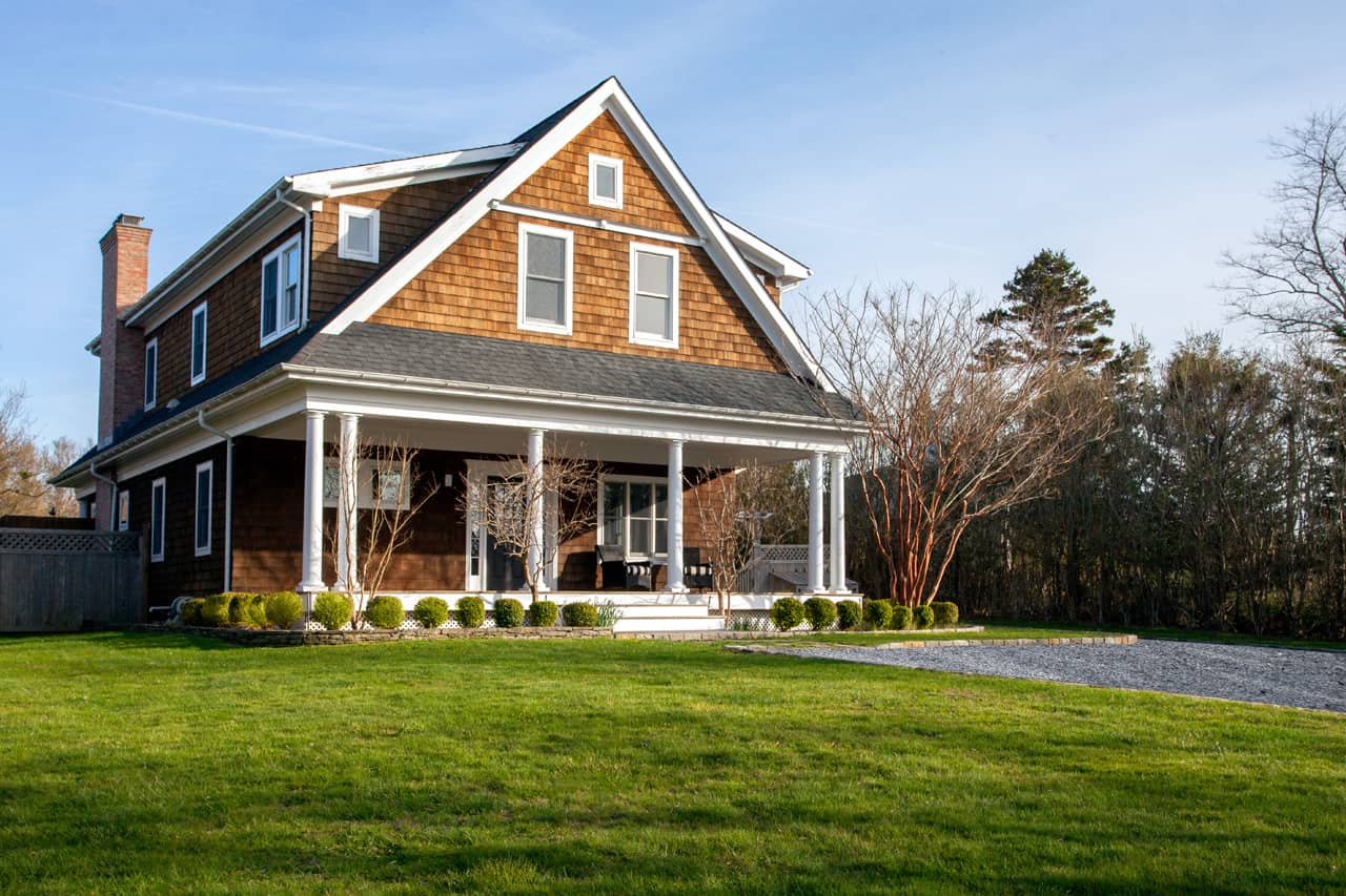 the-green-lawn-and-a-gravel-driveway-sit-in-front-of-the-house