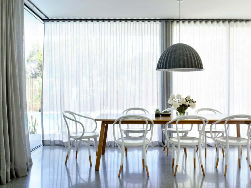 A light spacious dining area curtained from glazed walls