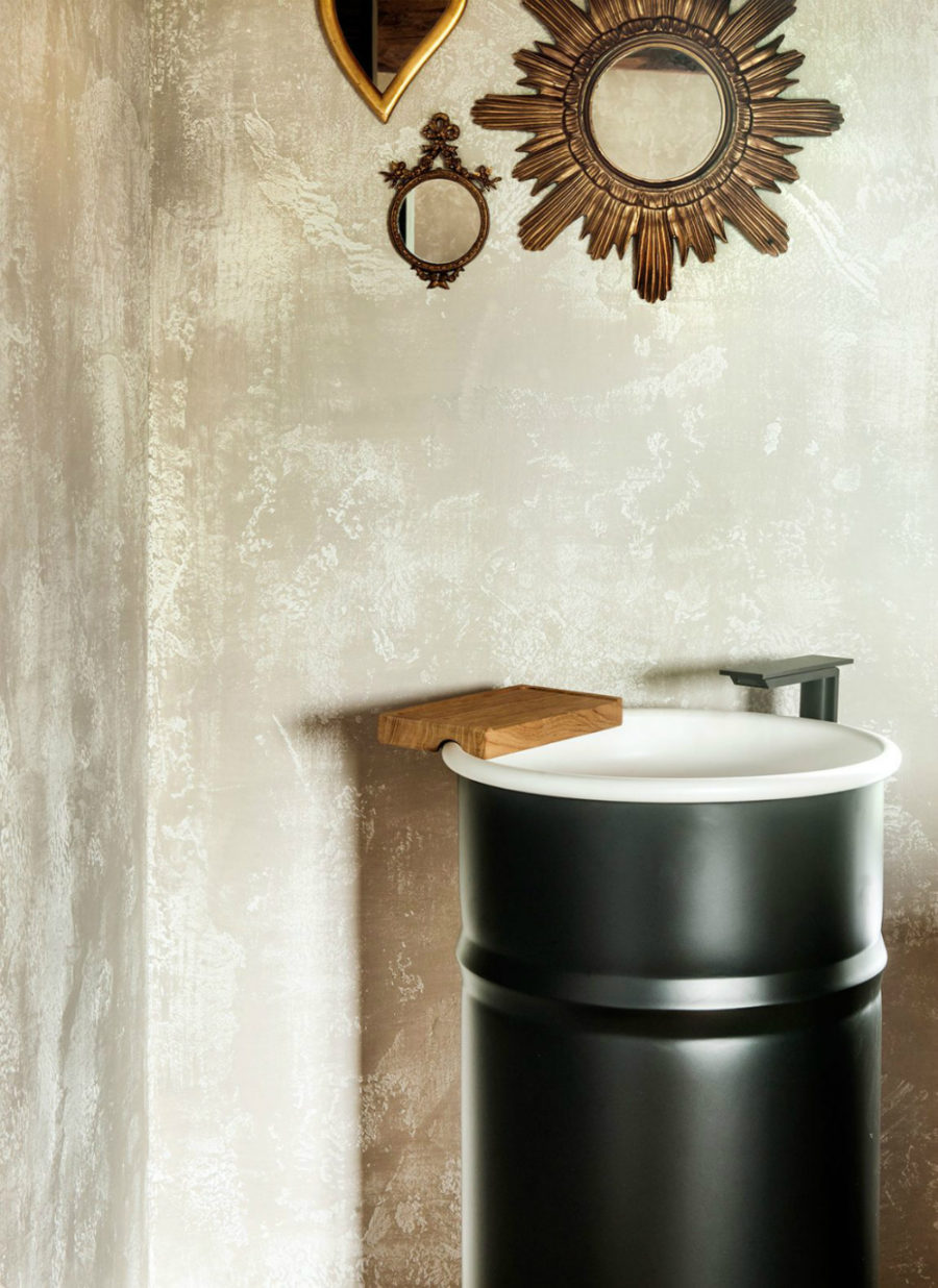 Barrel-shaped sink behind the bed