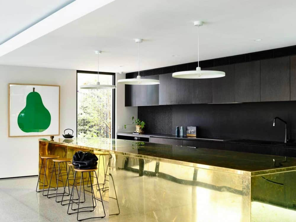 Contemporary kitchen with black cabinets and golden kitchen island