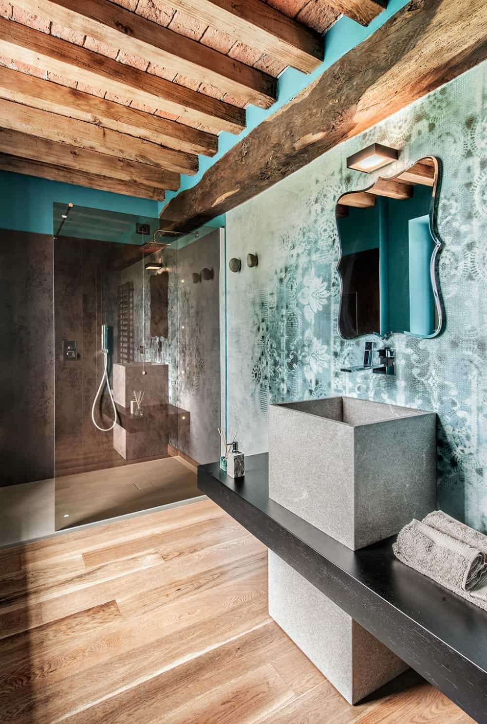 Fading lace patterns contrast with the worn wooden beams in the second bathroom
