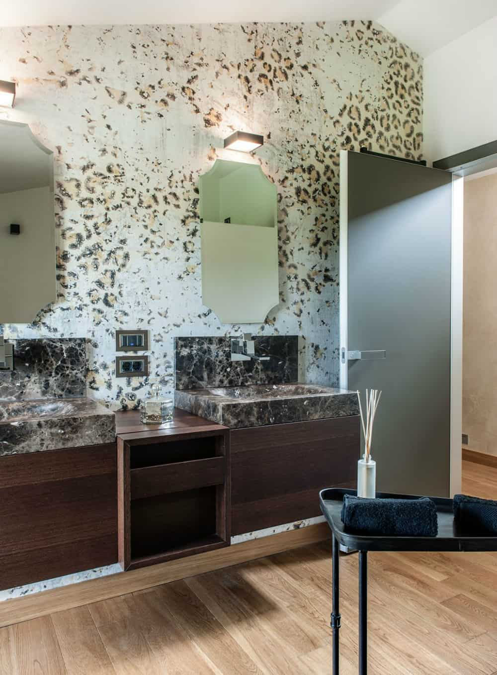 Marble sinks play along the cheetah-patterned walls