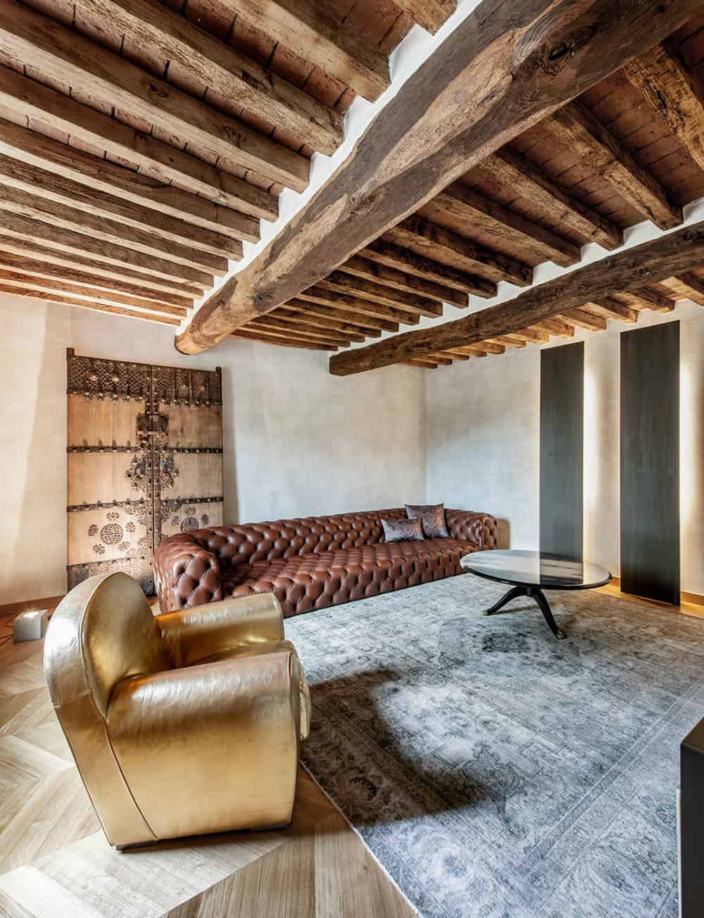 Old ornamental wooden door serves as the backdrop for the sofa
