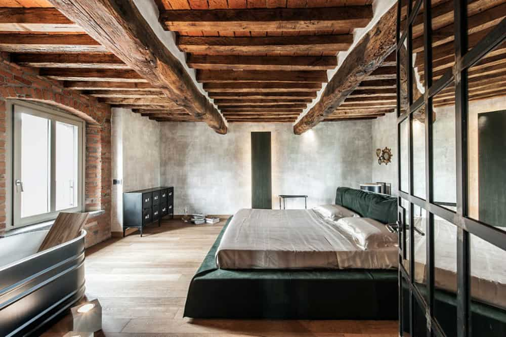 The giant bedroom has a huge soft bed frame and a metallic-shelled bathtub