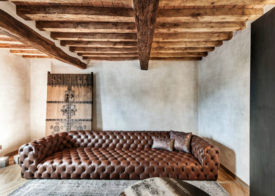Tufted leather sofa under old wooden beams 900x641 This Rustic Modern Home in Italy is Impossibly Luxurious