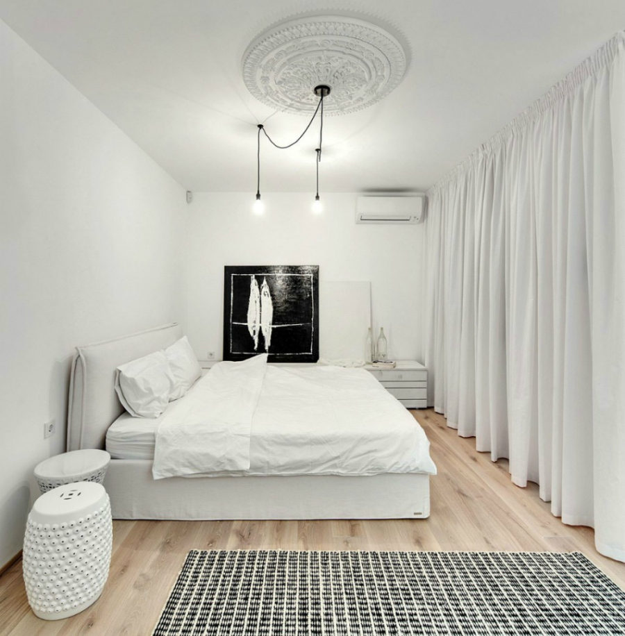 White bedroom with a soft bed and a ceiling medallion