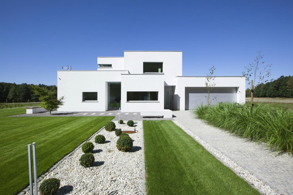 White facade with groomed lawns and waterless garden