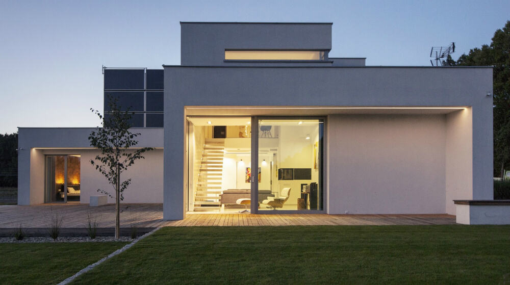 Yellow lighting gives warmth to the white concrete abode