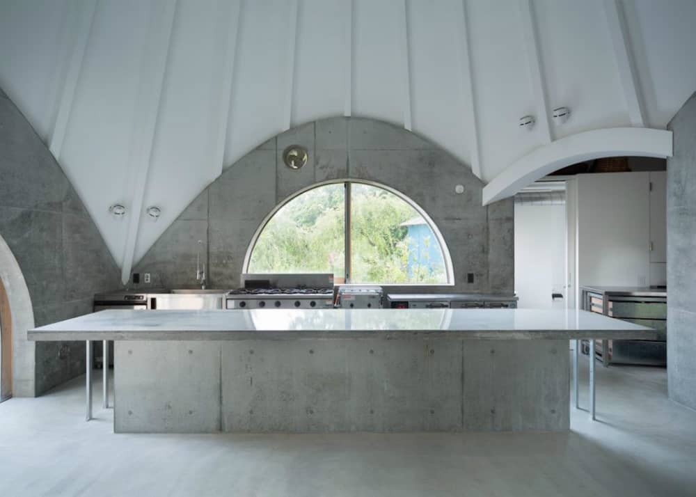 A big concrete kitchen island is a work space for one of the residents who's cook