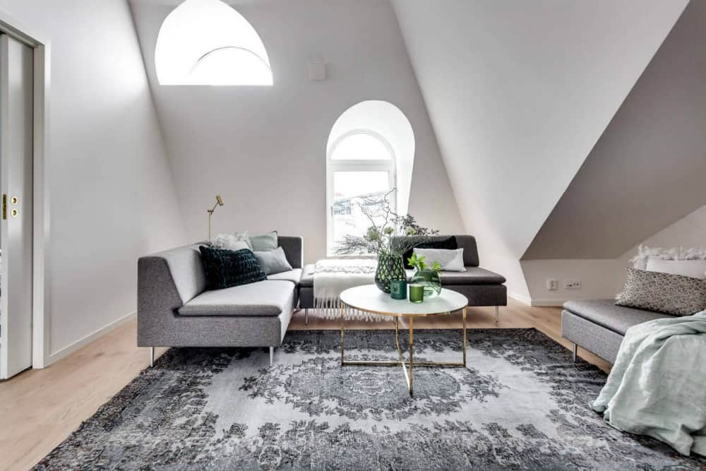 Arched windows flood the white living room with light
