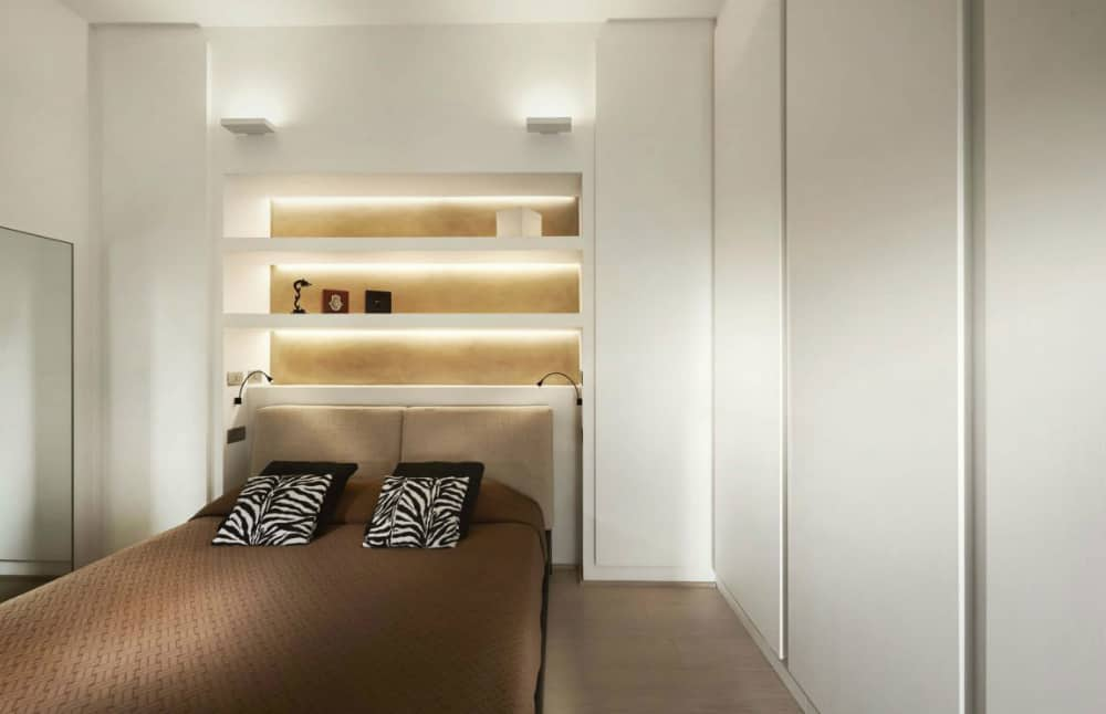 Bedroom with built-in headboard shelving