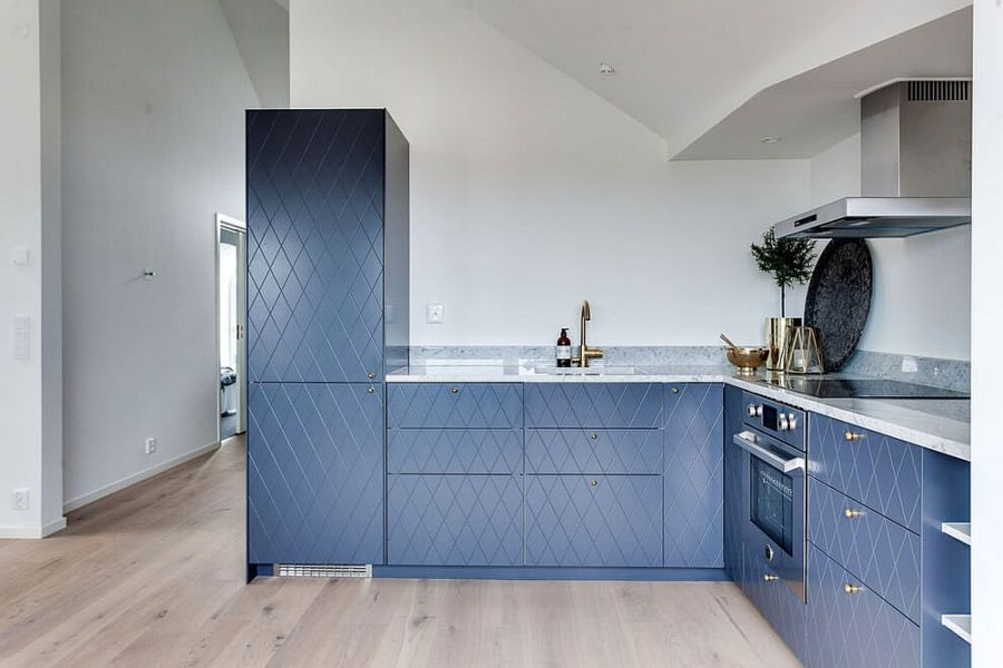 Blue kitchen cabinets make for a contrast in the white interior