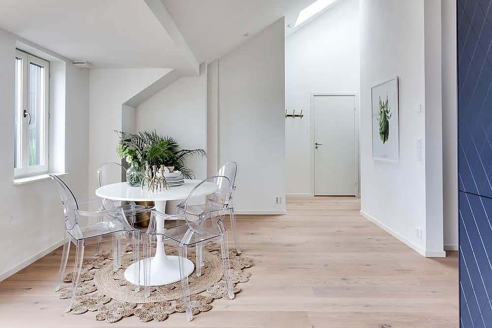 Lucite dining chairs create an airy atmosphere in the white room