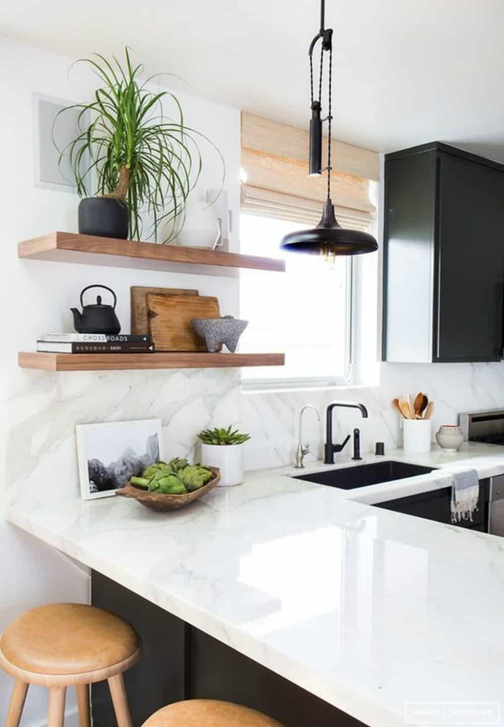 Monochromatic kitchen with a peninsula by Amber Interiors