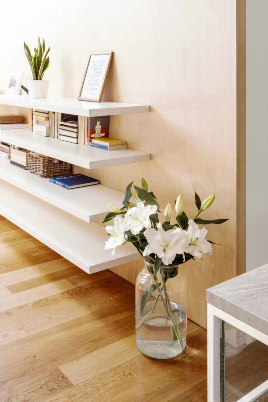 Open shelving provides storage for a home office across the seating room