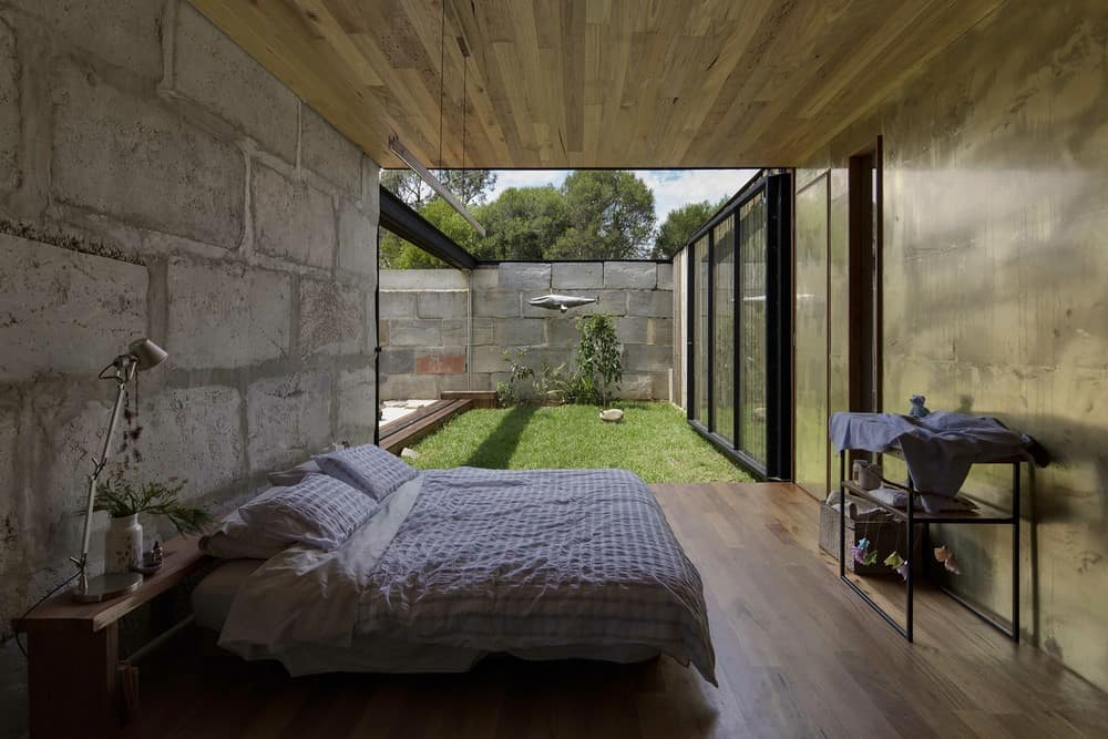 Part wooden, part brass bedroom with a concrete wall