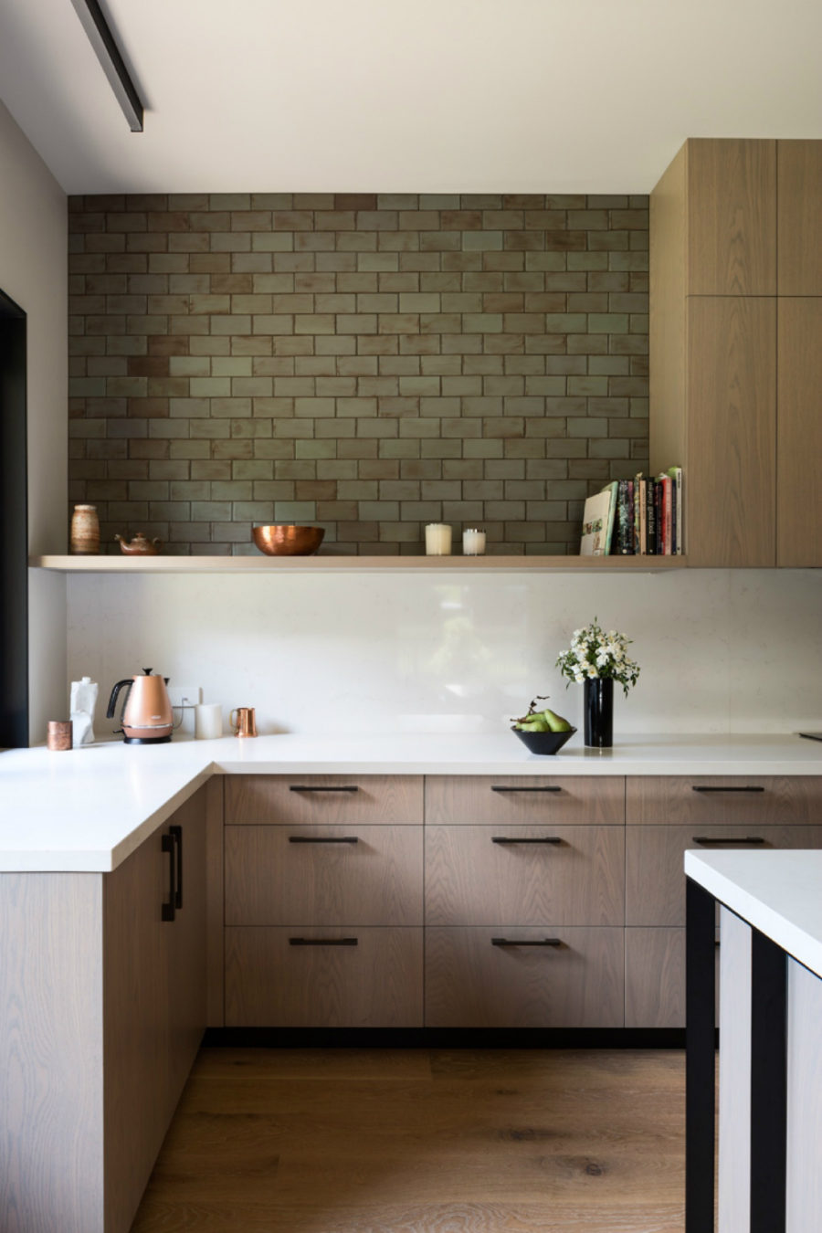 Simple kitchen design involves Corian countertops and upper shelves