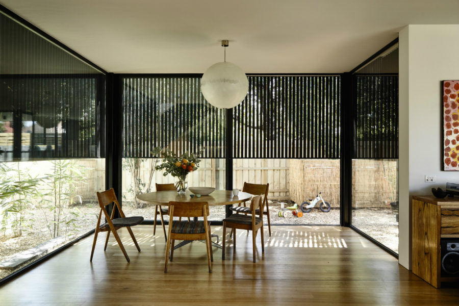 The dining area partially protected with a black wooden screen 900x600 Modernized 19th Century House With a Contemporary Timber Extension