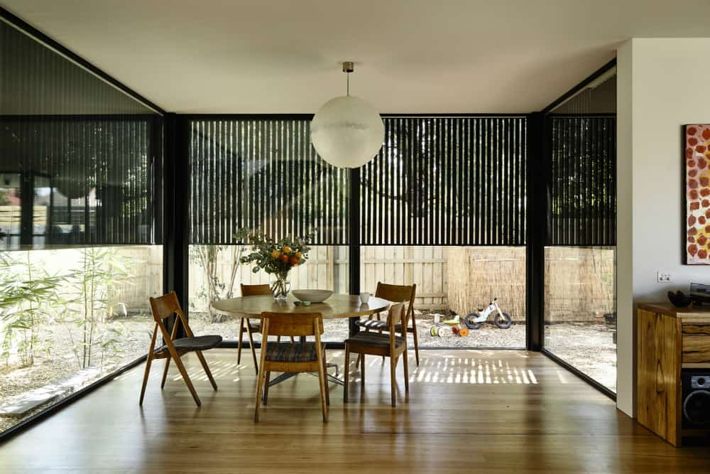 The dining area partially protected with a black wooden screen