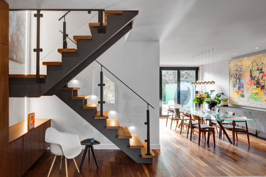 Wood and steel staircase features glass railing for an airier atmosphere
