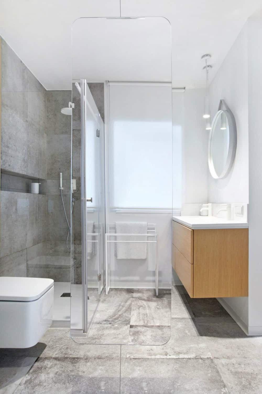 A rounded angle glass divider demarcates areas in the bathroom