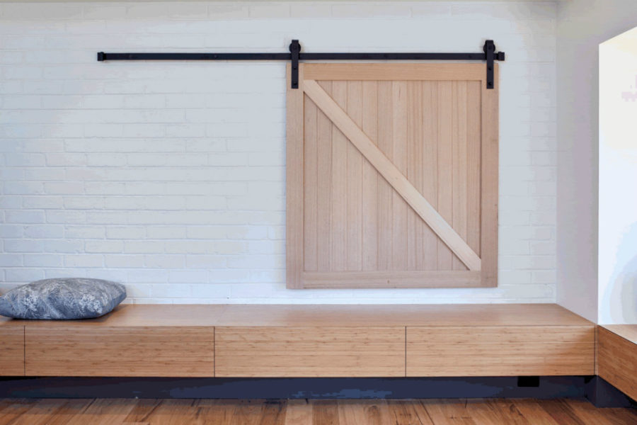 A small sliding barn door hides a window to another room